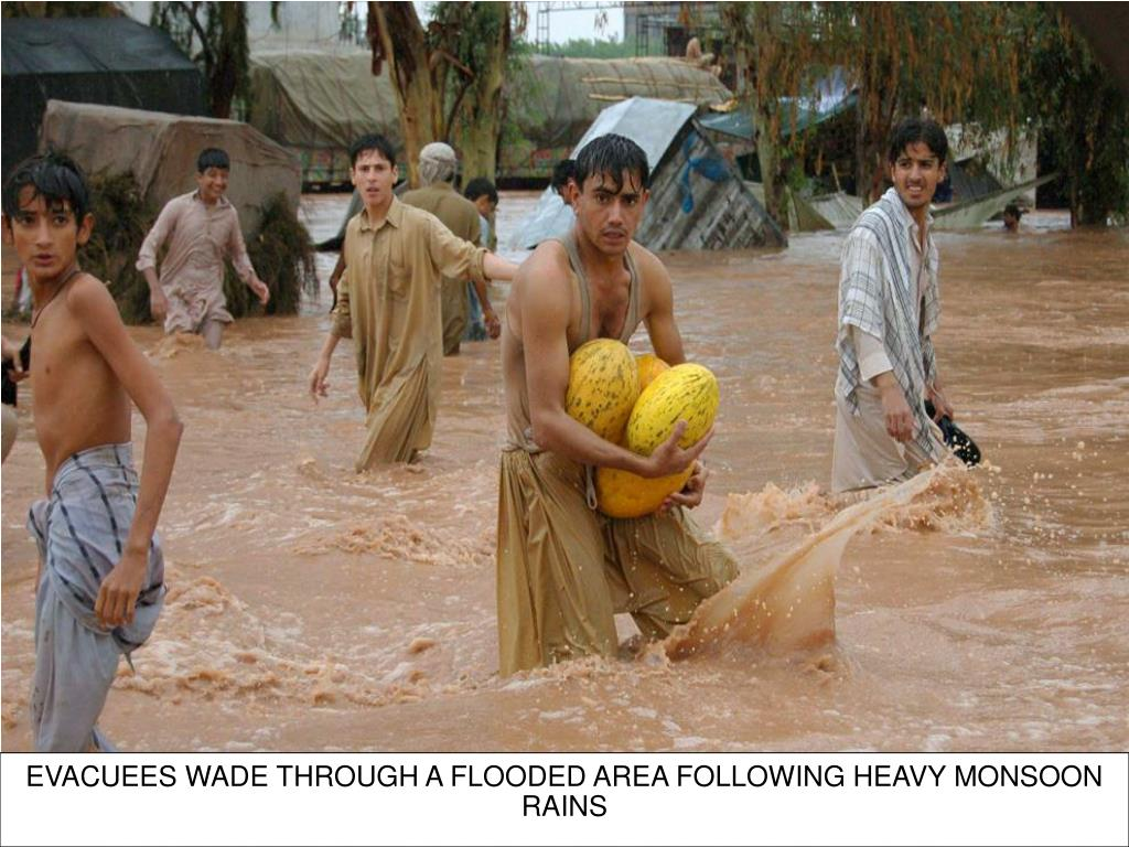EVACUEES WADE THROUGH A FLOODED AREA FOLLOWING HEAVY MONSOON RAINS