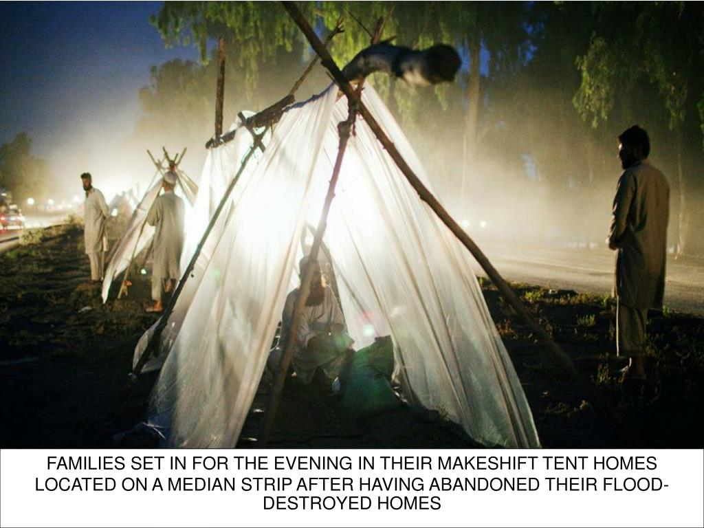 FAMILIES SET IN FOR THE EVENING IN THEIR MAKESHIFT TENT HOMES LOCATED ON A MEDIAN STRIP AFTER HAVING ABANDONED THEIR FLOOD-DESTROYED HOMES