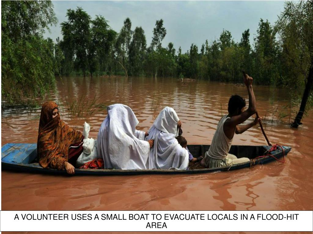 A VOLUNTEER USES A SMALL BOAT TO EVACUATE LOCALS IN A FLOOD-HIT AREA