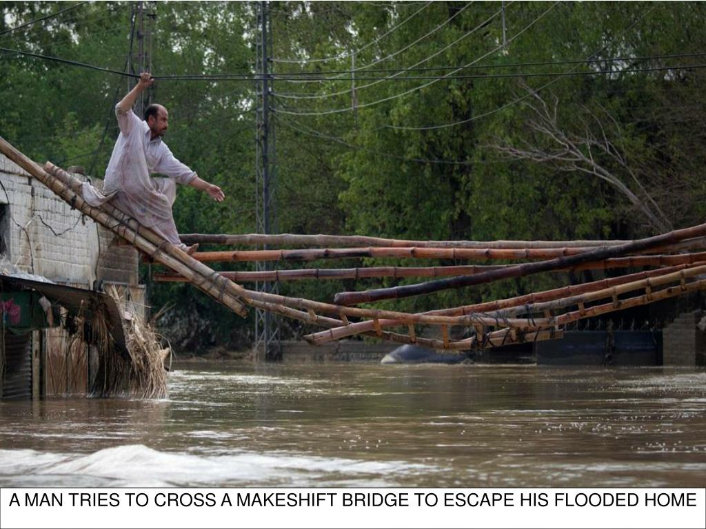 A MAN TRIES TO CROSS A MAKESHIFT BRIDGE TO ESCAPE HIS FLOODED HOME