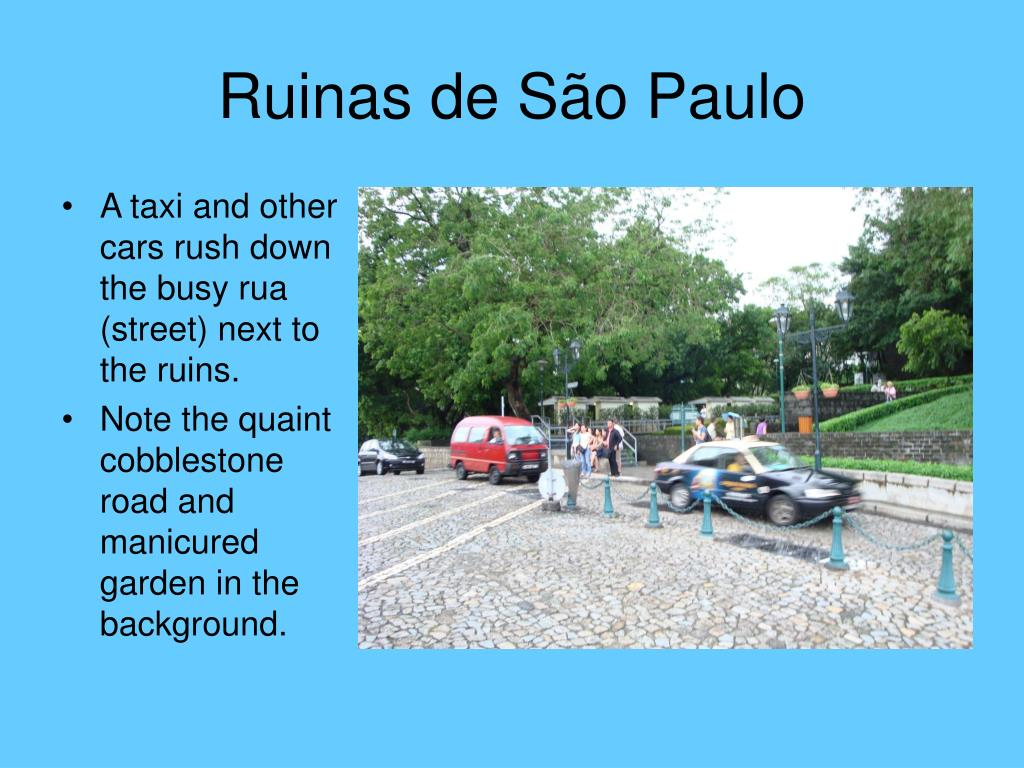 A taxi and other cars rush down the busy rua (street) next to the ruins.