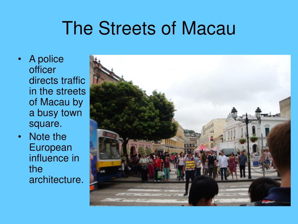 A police officer directs traffic in the streets of Macau by a busy town square.