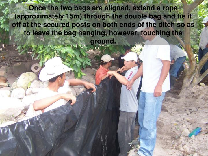 Once the two bags are aligned, extend a rope (approximately 15m) through the double bag and tie it off at the secured posts on both ends of the ditch so as to leave the bag hanging, however, touching the ground.