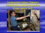 cosmonaut valery tokarev installs the hardware on the orlan space suit