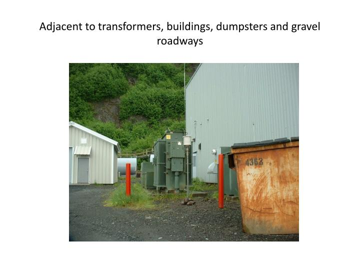 Adjacent to transformers, buildings, dumpsters and gravel roadways