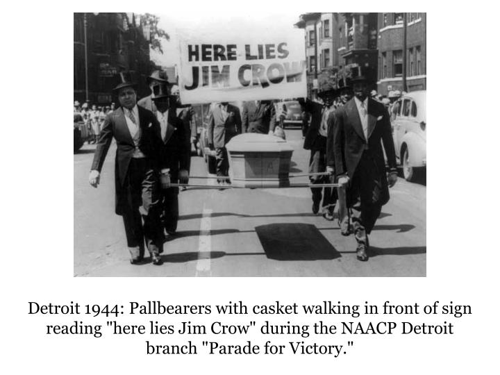 """Detroit 1944: Pallbearers with casket walking in front of sign reading """"here lies Jim Crow"""" during the NAACP Detroit branch """"Parade for Victory."""""""