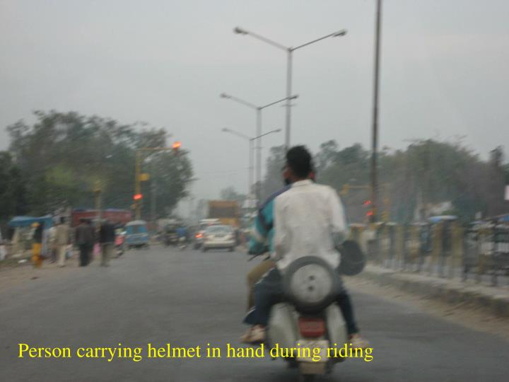 Person carrying helmet in hand during riding