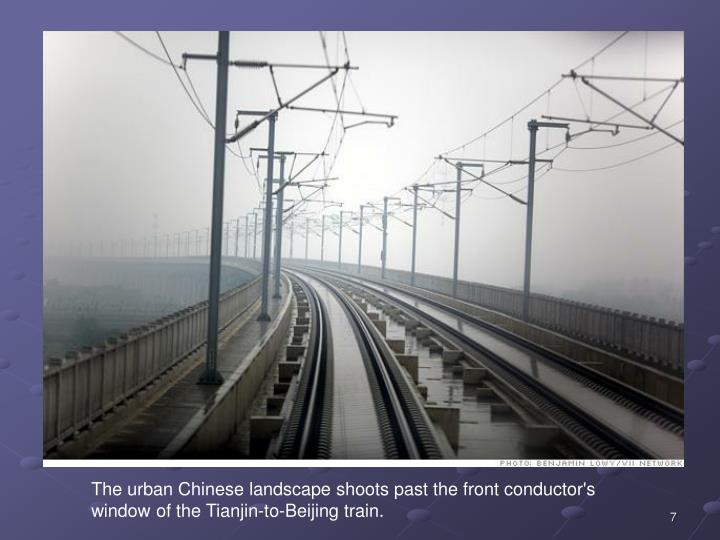 The urban Chinese landscape shoots past the front conductor's window of the Tianjin-to-Beijing train.