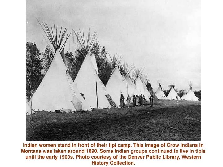 Indian women stand in front of their tipi camp. This image of Crow Indians in Montana was taken arou...