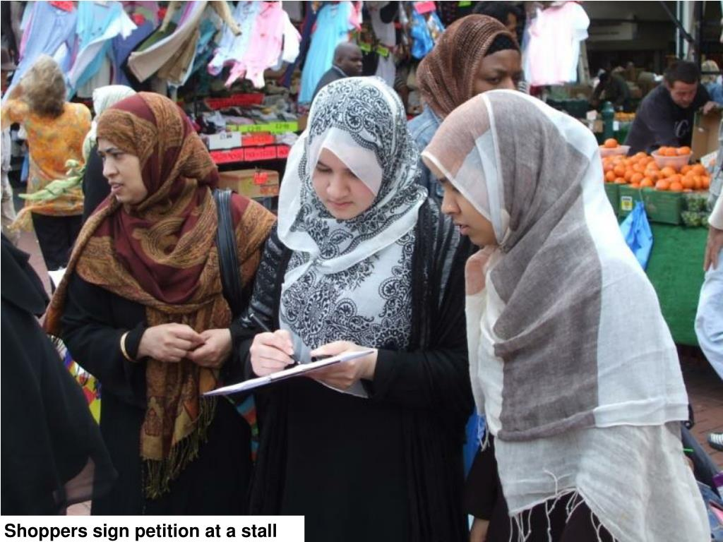 Shoppers sign petition at a stall