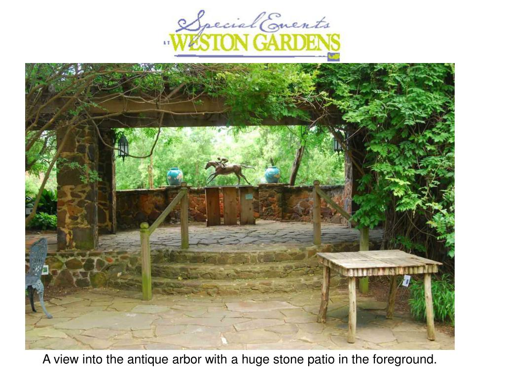 A view into the antique arbor with a huge stone patio in the foreground.
