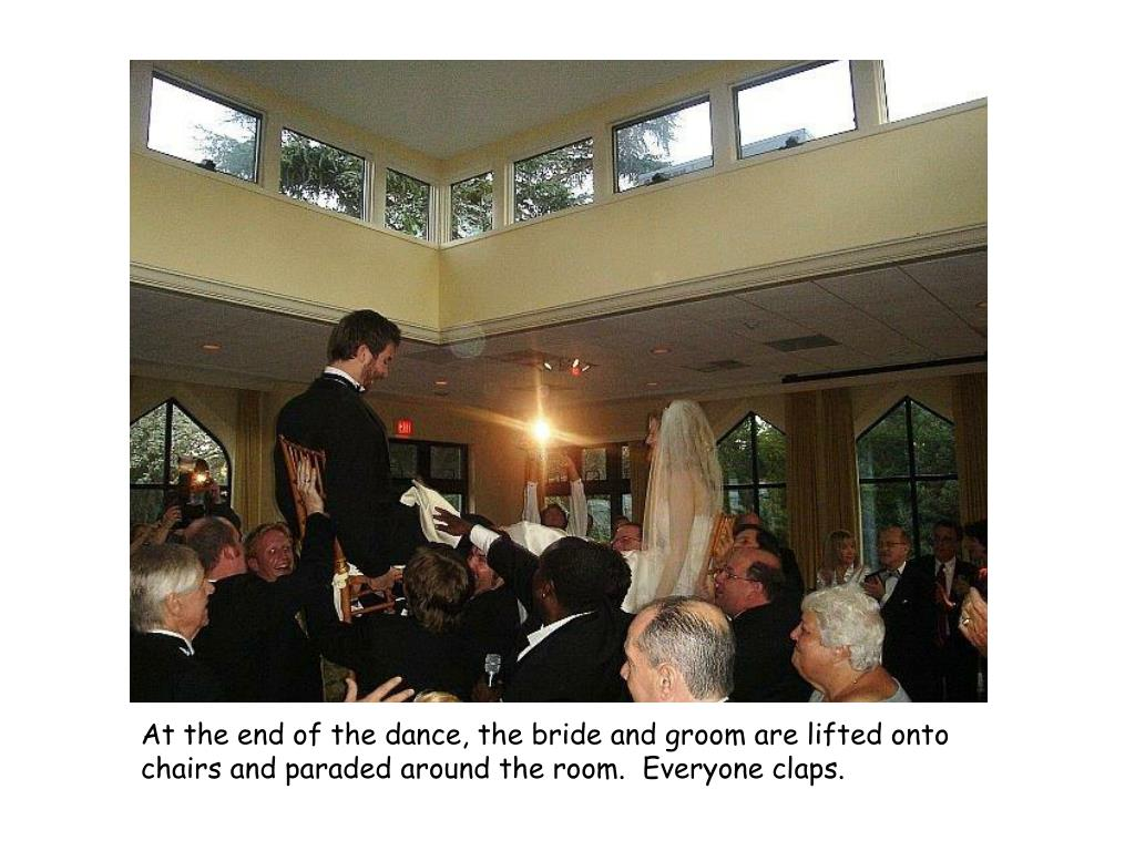 At the end of the dance, the bride and groom are lifted onto chairs and paraded around the room.  Everyone claps.