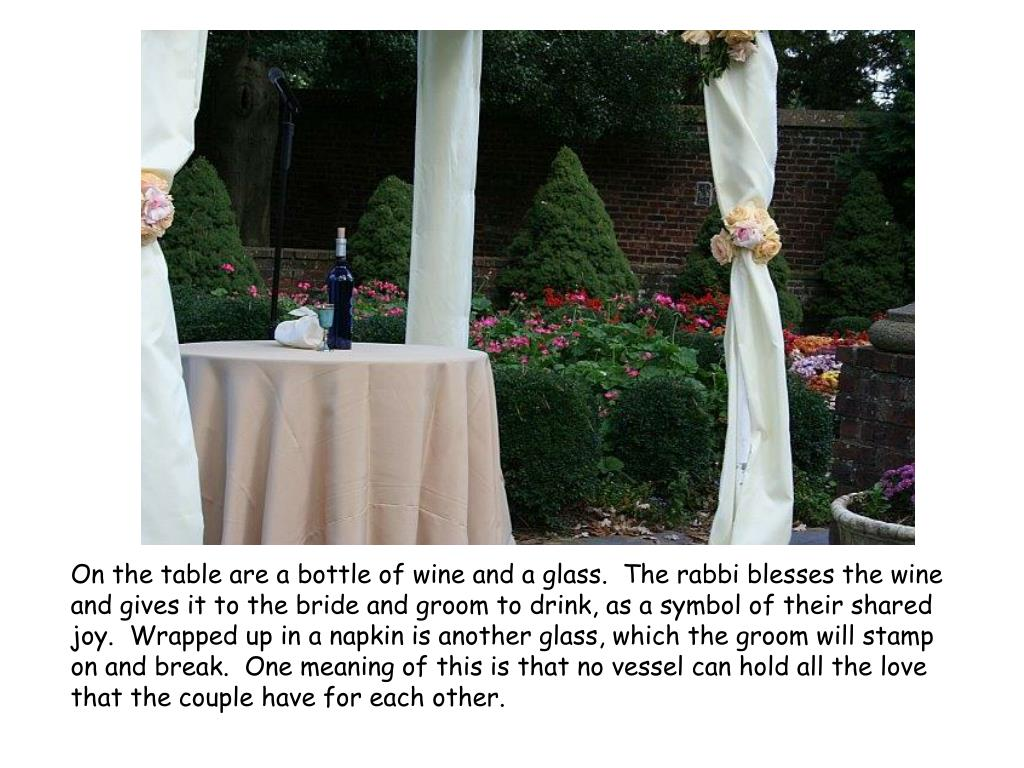 On the table are a bottle of wine and a glass.  The rabbi blesses the wine and gives it to the bride and groom to drink, as a symbol of their shared joy.  Wrapped up in a napkin is another glass, which the groom will stamp on and break.  One meaning of this is that no vessel can hold all the love that the couple have for each other.