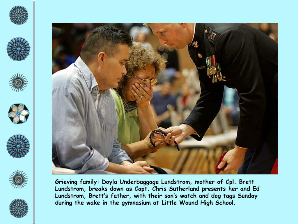 Grieving family: Doyla Underbaggage Lundstrom, mother of Cpl. Brett Lundstrom, breaks down as Capt. Chris Sutherland presents her and Ed Lundstrom, Brett's father, with their son's watch and dog tags Sunday during the wake in the gymnasium at Little Wound High School.