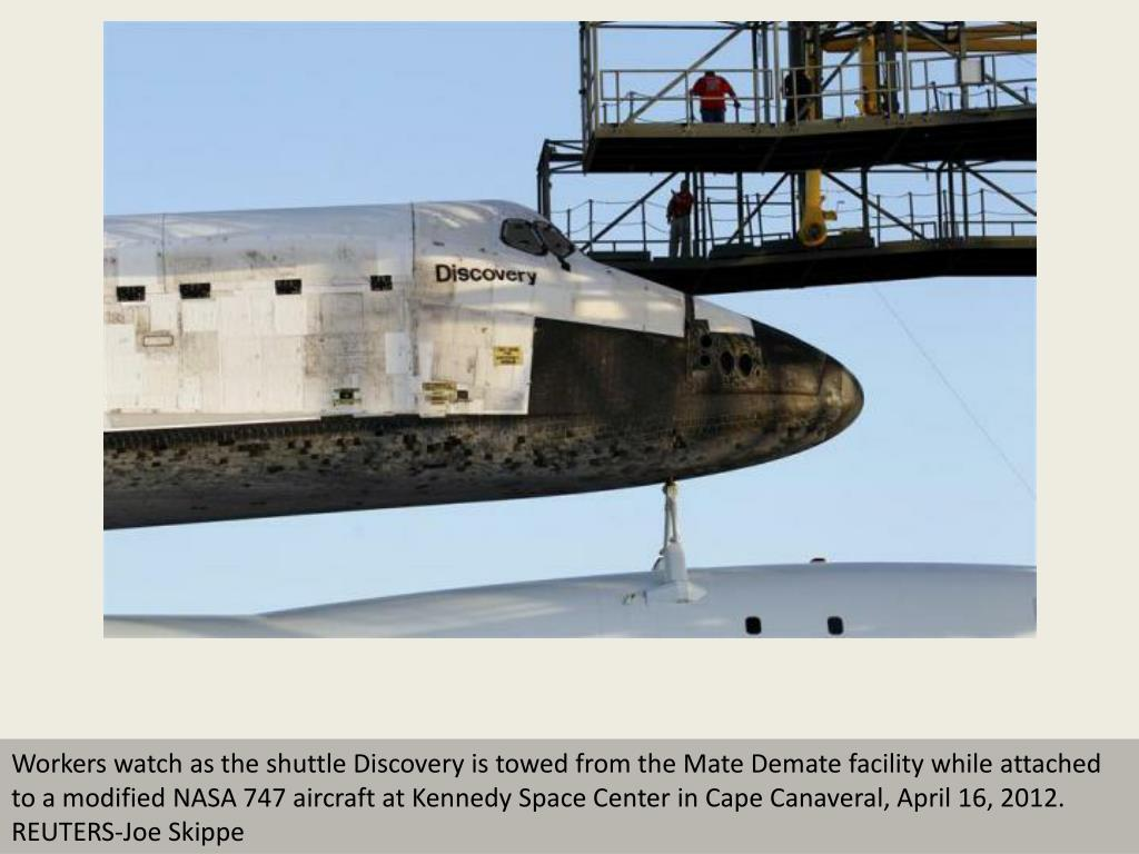 Workers watch as the shuttle Discovery is towed from the Mate Demate facility while attached to a modified NASA 747 aircraft at Kennedy Space Center in Cape Canaveral, April 16, 2012.  REUTERS-Joe Skippe