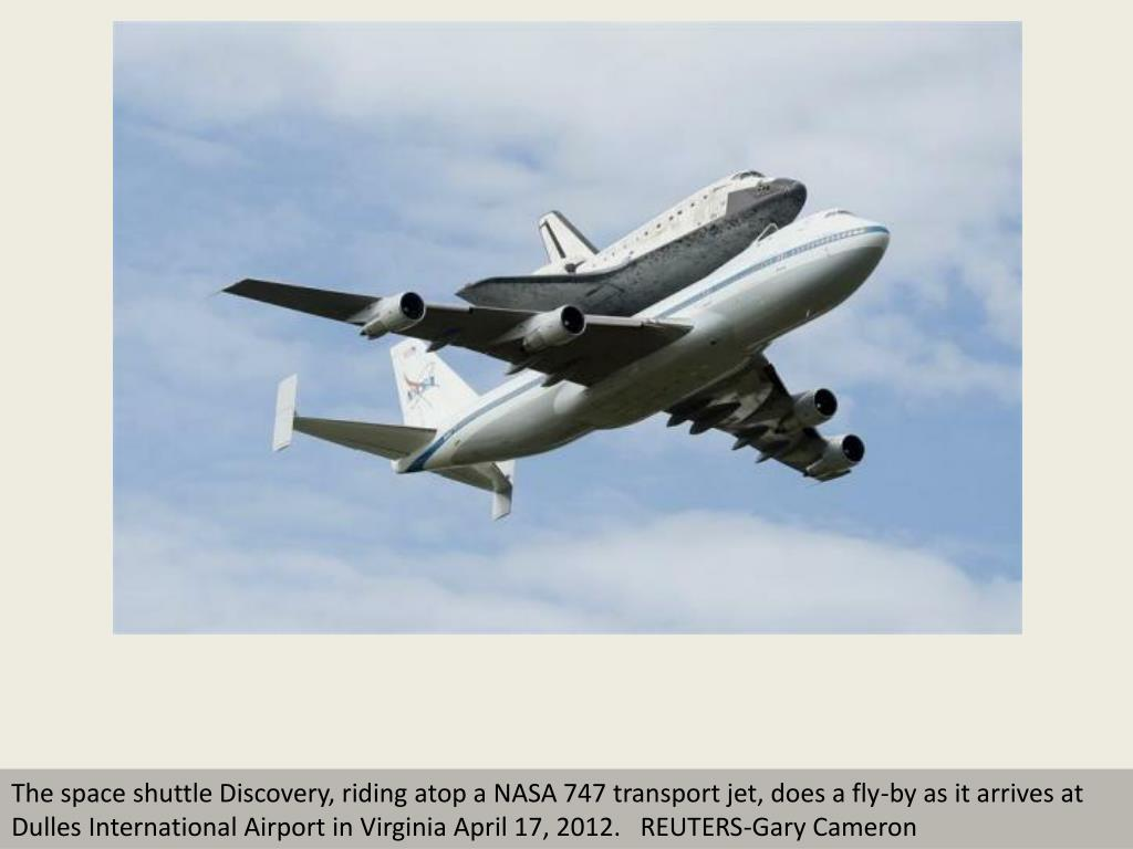 The space shuttle Discovery, riding atop a NASA 747 transport jet, does a fly-by as it arrives at Dulles International Airport in Virginia April 17, 2012.   REUTERS-Gary Cameron