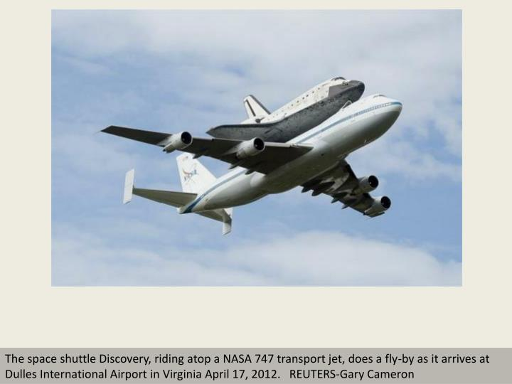 The space shuttle Discovery, riding atop a NASA 747 transport jet, does a fly-by as it arrives at Du...