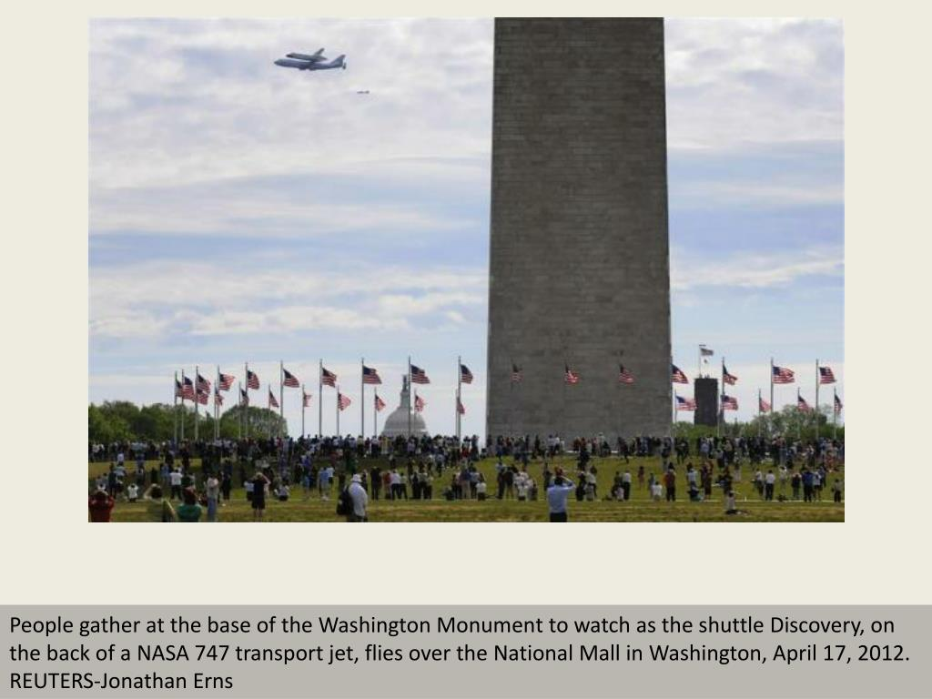People gather at the base of the Washington Monument to watch as the shuttle Discovery, on the back of a NASA 747 transport jet, flies over the National Mall in Washington, April 17, 2012.  REUTERS-Jonathan Erns