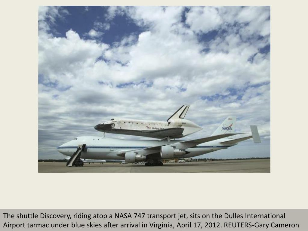 The shuttle Discovery, riding atop a NASA 747 transport jet, sits on the Dulles International Airport tarmac under blue skies after arrival in Virginia, April 17, 2012. REUTERS-Gary Cameron