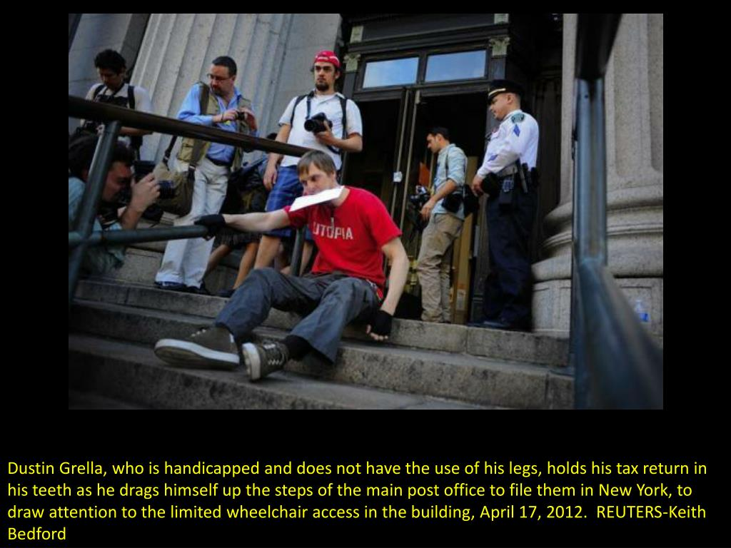 Dustin Grella, who is handicapped and does not have the use of his legs, holds his tax return in his teeth as he drags himself up the steps of the main post office to file them in New York, to draw attention to the limited wheelchair access in the building, April 17, 2012.  REUTERS-Keith Bedford