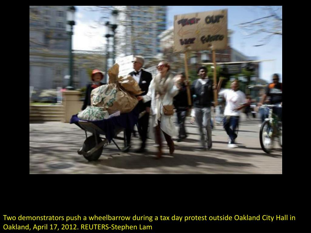 Two demonstrators push a wheelbarrow during a tax day protest outside Oakland City Hall in Oakland, April 17, 2012. REUTERS-Stephen Lam