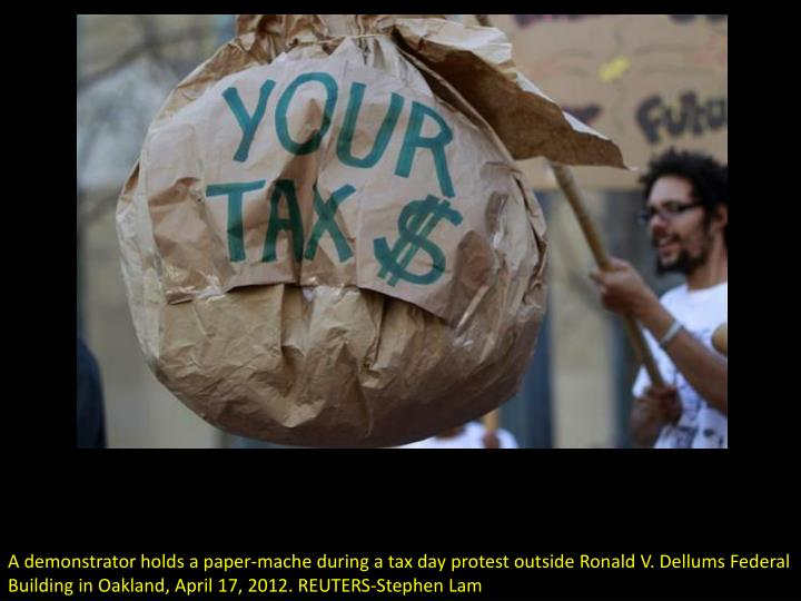 A demonstrator holds a paper-mache during a tax day protest outside Ronald V. Dellums Federal Buildi...