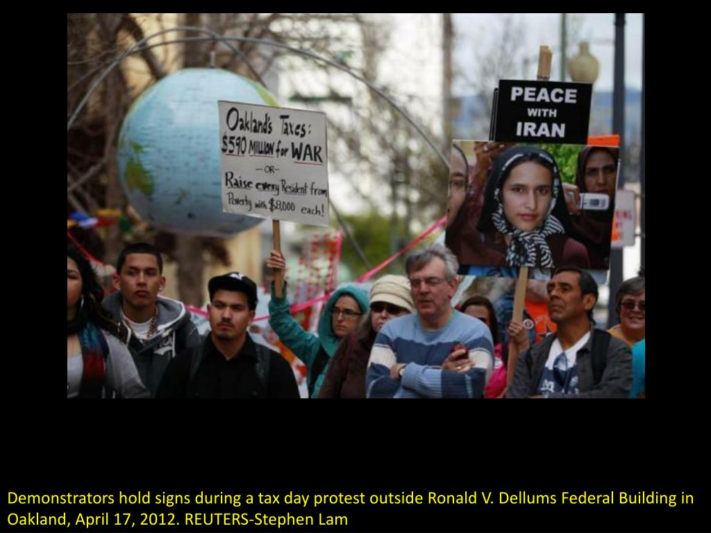 Demonstrators hold signs during a tax day protest outside Ronald V. Dellums Federal Building in Oakland, April 17, 2012. REUTERS-Stephen Lam