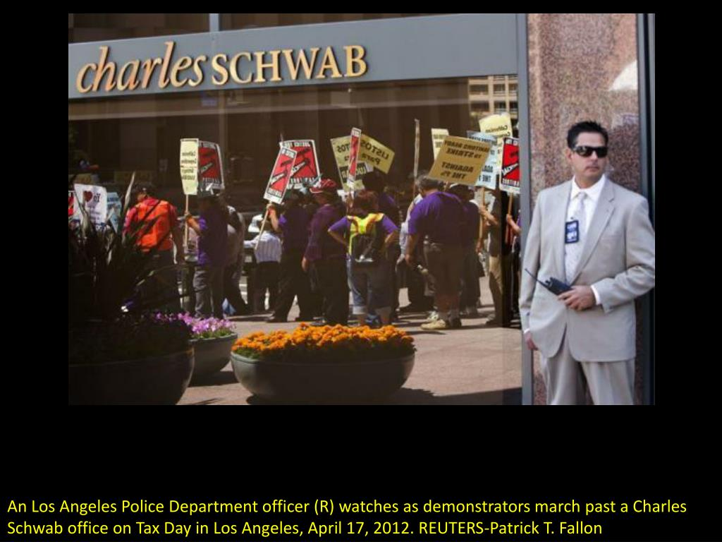 An Los Angeles Police Department officer (R) watches as demonstrators march past a Charles Schwab office on Tax Day in Los Angeles, April 17, 2012. REUTERS-Patrick T. Fallon