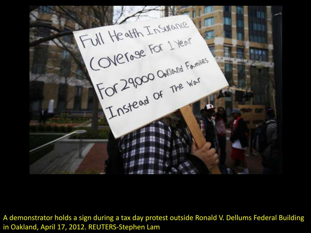 A demonstrator holds a sign during a tax day protest outside Ronald V. Dellums Federal Building in Oakland, April 17, 2012. REUTERS-Stephen Lam