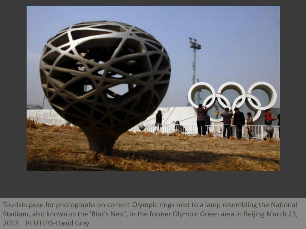 Tourists pose for photographs on cement Olympic rings next to a lamp resembling the National Stadium, also known as the 'Bird's Nest', in the former Olympic Green area in Beijing March 23, 2012.   REUTERS-David Gray