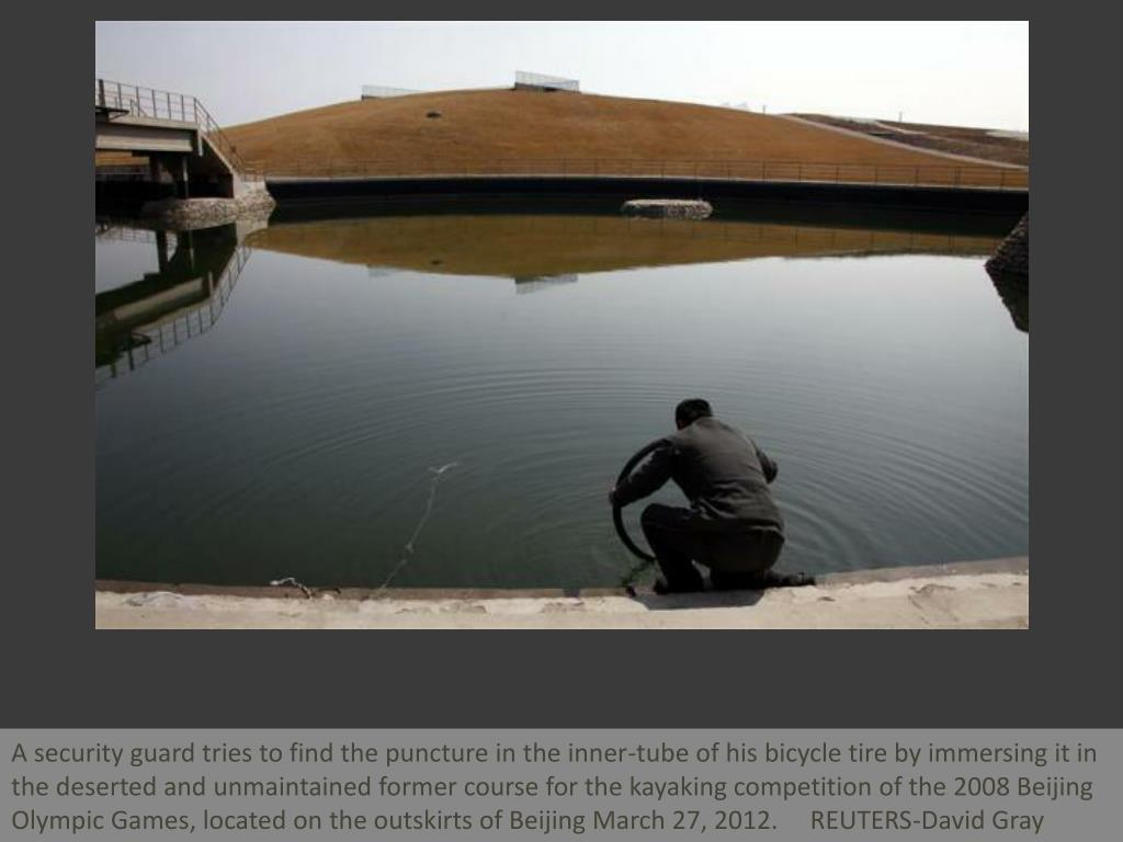 A security guard tries to find the puncture in the inner-tube of his bicycle tire by immersing it in the deserted and unmaintained former course for the kayaking competition of the 2008 Beijing Olympic Games, located on the outskirts of Beijing March 27, 2012.     REUTERS-David Gray