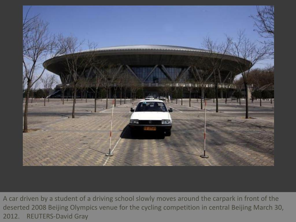 A car driven by a student of a driving school slowly moves around the carpark in front of the deserted 2008 Beijing Olympics venue for the cycling competition in central Beijing March 30, 2012.    REUTERS-David Gray