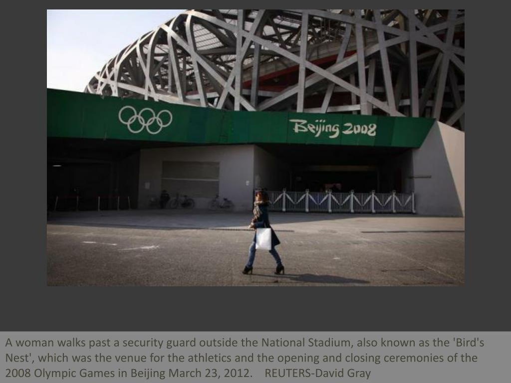 A woman walks past a security guard outside the National Stadium, also known as the 'Bird's Nest', which was the venue for the athletics and the opening and closing ceremonies of the 2008 Olympic Games in Beijing March 23, 2012.    REUTERS-David Gray