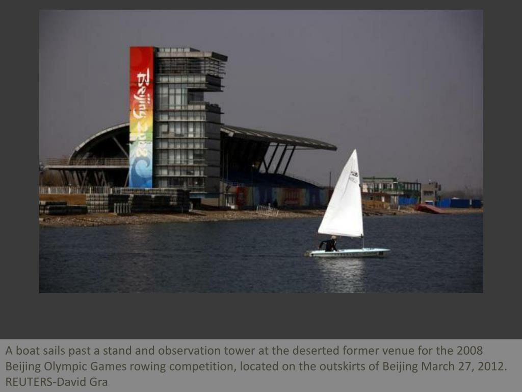 A boat sails past a stand and observation tower at the deserted former venue for the 2008 Beijing Olympic Games rowing competition, located on the outskirts of Beijing March 27, 2012.    REUTERS-David Gra