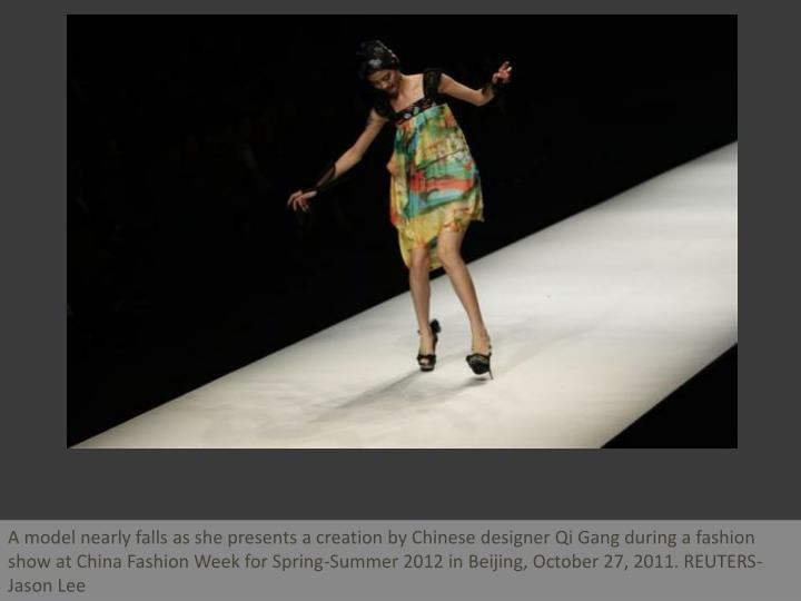 A model nearly falls as she presents a creation by Chinese designer Qi Gang during a fashion show at...