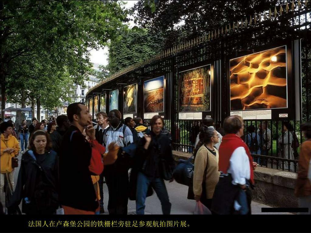 法国人在卢森堡公园的铁栅栏旁驻足参观航拍图片展。