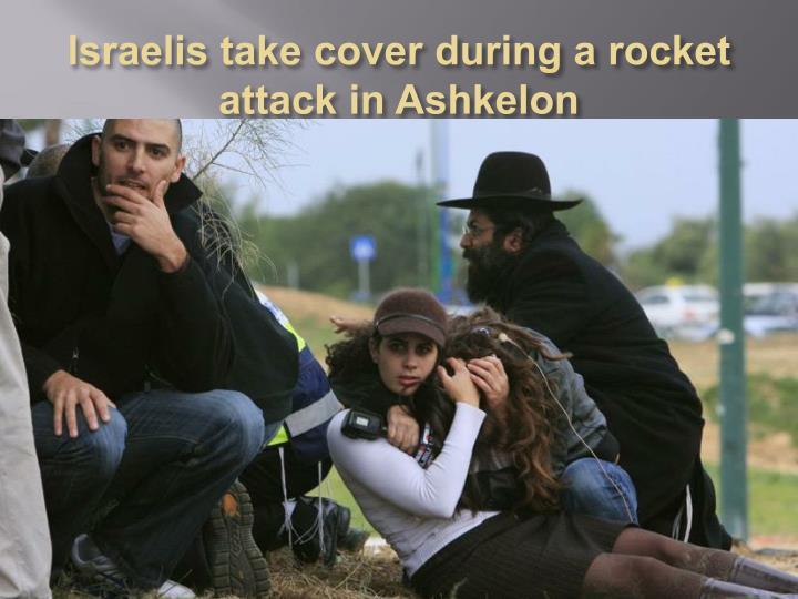 Israelis take cover during a rocket attack in Ashkelon