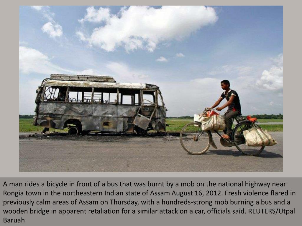 A man rides a bicycle in front of a bus that was burnt by a mob on the national highway near Rongia town in the northeastern Indian state of Assam August 16, 2012. Fresh violence flared in previously calm areas of Assam on Thursday, with a hundreds-strong mob burning a bus and a wooden bridge in apparent retaliation for a similar attack on a car, officials said. REUTERS/Utpal Baruah