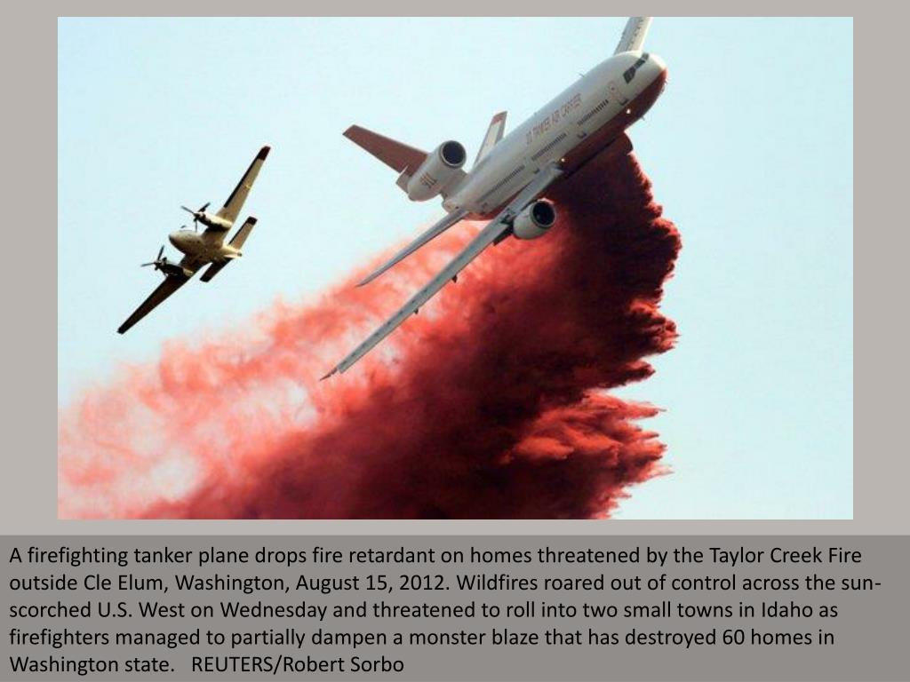 A firefighting tanker plane drops fire retardant on homes threatened by the Taylor Creek Fire outside Cle Elum, Washington, August 15, 2012. Wildfires roared out of control across the sun-scorched U.S. West on Wednesday and threatened to roll into two small towns in Idaho as firefighters managed to partially dampen a monster blaze that has destroyed 60 homes in Washington state.   REUTERS/Robert Sorbo