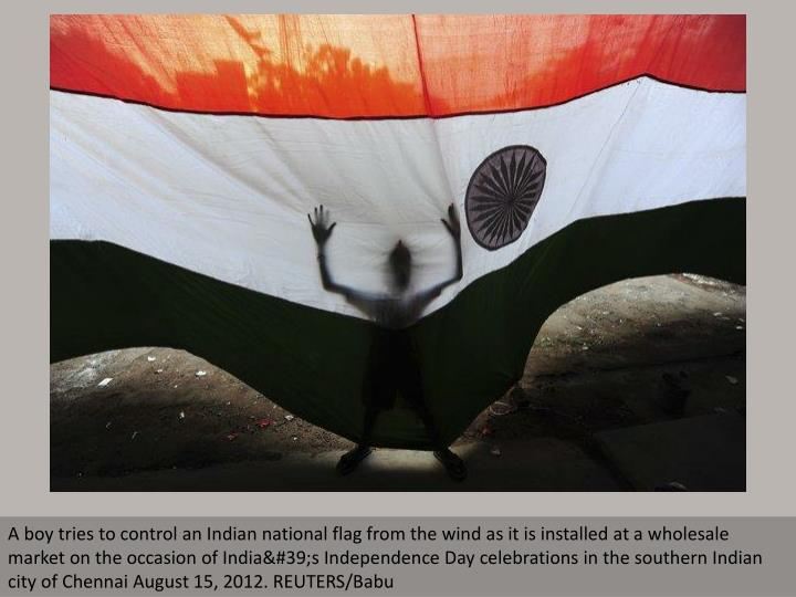 A boy tries to control an Indian national flag from the wind as it is installed at a wholesale marke...