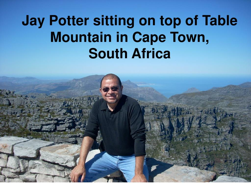 Jay Potter sitting on top of Table Mountain in Cape Town,