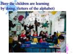 here the children are learning by doing letters of the alphabet