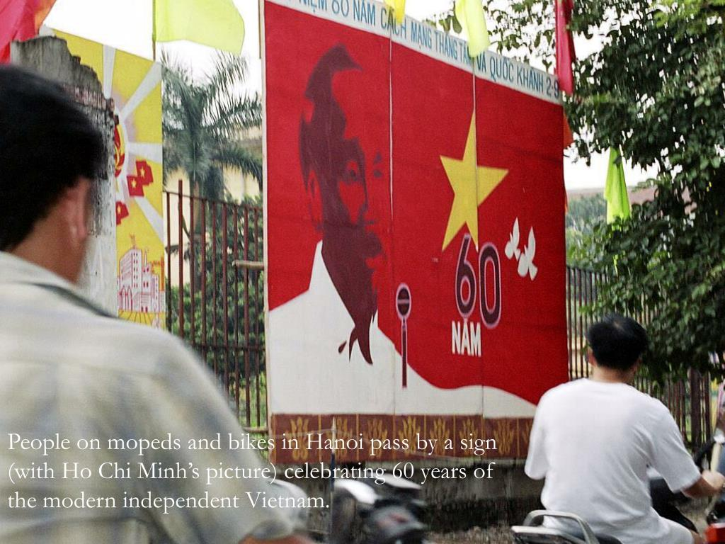 People on mopeds and bikes in Hanoi pass by a sign (with Ho Chi Minh's picture) celebrating 60 years of the modern independent Vietnam.